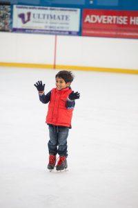 boy laughing and waving - ice skating